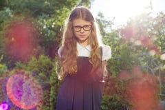 Utomhus- st?ende av h?rlig flicka 7, 8 gamla ?r med exponeringsglasskolalikformign royaltyfri foto