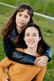 Utomhus- stående av två kopplade av lyckliga systrar Royaltyfri Bild