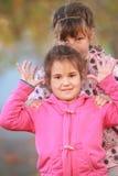 Utomhus- stående av två unga lyckliga barn, flickor - systrar - Arkivfoton