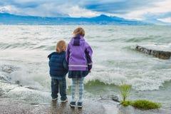 Utomhus- stående av två ungar som spelar vid sjön Arkivbild