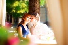 Utomhus- stående av unga sinnliga par i sommarkafé Älska Fotografering för Bildbyråer