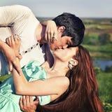 Utomhus- stående för sommar av ungt kyssa för par Arkivbild