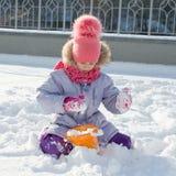 Utomhus- stående för vinter av barnflickan som ler och spelar med snö, ljus solig vinterdag arkivbilder