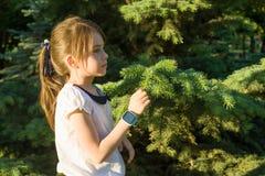 Utomhus- stående i profil av en flicka av 7 år Kopieringsutrymme, grönt träd för bakgrund arkivfoto