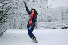 Utomhus ståenden av att le unga flickan som bär den röda halsduken och har den roliga yttersidan i det snöig, parkerar under vint Royaltyfria Bilder