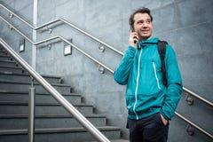 Utomhus- st?ende av den moderna unga mannen med mobiltelefonen arkivbild