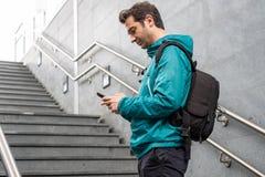 Utomhus- st?ende av den moderna unga mannen med mobiltelefonen royaltyfria bilder