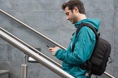 Utomhus- st?ende av den moderna unga mannen med mobiltelefonen royaltyfri bild