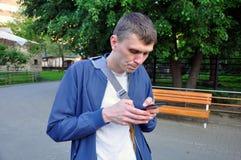 Utomhus- st?ende av den moderna unga mannen med mobiltelefonen i gatan royaltyfri bild
