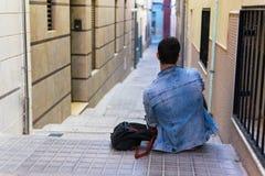 Utomhus- st?ende av den moderna unga mannen med den smarta telefonen som sitter i gatan arkivfoton