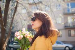 Utomhus st?ende av den stilfulla attraktiva brunettkvinnan i solglas?gon som utomhus g?r med den stora buketten av f?rgrikt arkivfoto