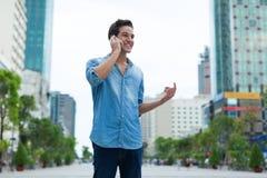 Utomhus- stad för stiligt leende för manmobiltelefonappell arkivfoto