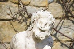 Utomhus- stena statyn av den roliga gamala mannen arkivfoton