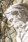 Utomhus- stena statyn av gamala mannen med skägget och hatten arkivfoto