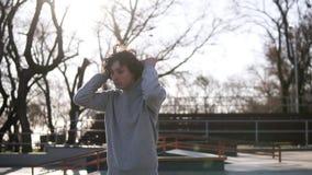 Utomhus- stiliga ung mans stående Den ton?riga pojken i hoodie som g?r ?ver v?rskridsko, parkerar med naturbakgrund grabb lager videofilmer