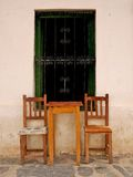 Utomhus- tabell och stolar framme av huset Arkivfoto