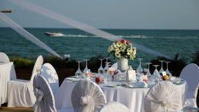Utomhus- tabellinställning på bröllopmottagandet vid havet stock video