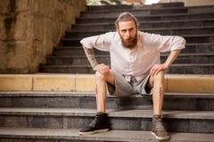 Utomhus- Tattoed och skäggigt posera för hipstergrabb royaltyfri foto