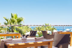 Utomhus- terrass av restaurangen som förbiser havet och palmträden arkivbilder