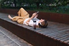 Utomhus- tonårs- kvinnlig lyssnande musik och att ligga på bänk och att koppla av? sommar Royaltyfria Bilder
