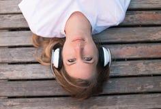 Utomhus- tonårs- kvinnlig lyssnande musik och att ligga på bänk och att koppla av? sommar Arkivbilder