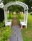 Utomhus- trädgårdvalvgång med bänkar royaltyfri fotografi