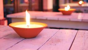 Utomhus- trätabeller med romantiska oljalampor som flammar på aftonen arkivfilmer