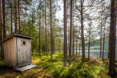 Utomhus- trätoalett i ett härligt soligt skogvildmarklandskap vid en sjö arkivfoton