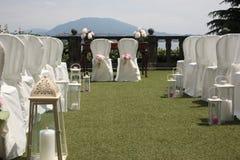 Utomhus- uppsättning för bröllopceremoni: linje av vita stolar med skrivbordet och stol för det gift och tjänstemannen royaltyfri foto