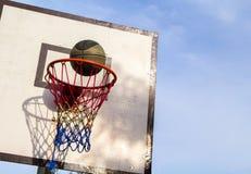 Utomhus- utrustning för basketmatch Korg och boll Exakt bollkast i korg arkivfoto