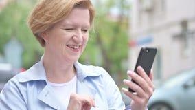 Utomhus- video pratstund via Smartphone av den gamla kvinnan lager videofilmer