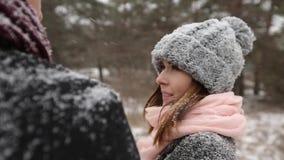 Utomhus- vinterskogskott av unga brölloppar som går, ler och talar i snöväderpinjeskog under
