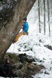 Utomhus- vintersport Vagga klättraren som stiger en utmanande klippa Extrem sportklättring royaltyfri bild