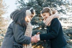 Utomhus- vinterstående av två små flickor som ler och har gyckel nära julgranen, guld- timme royaltyfria foton