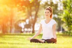utomhus- yoga Den lyckliga kvinnan som gör yogaövningar, mediterar Royaltyfria Bilder