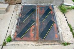 Utomhus- yttersida rostade dörrar till trappa till källaregolvet Arkivfoton
