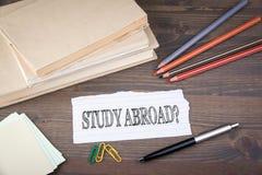 utomlands study pappers- ark från häftet på trätabellen Royaltyfria Bilder