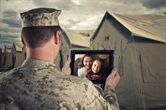 Utplacerade militära manpratstunder med familjen arkivfoto