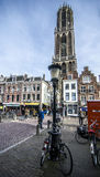Utrecht city center plaza with a lot of people walking during bautiful autumn day. Early Saturday morning in the city center where huge church is in the front Royalty Free Stock Photo