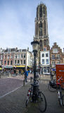Utrecht city center plaza with a lot of people walking during bautiful autumn day. Early Saturday morning in the city center where huge church is in the front Royalty Free Stock Photos