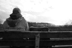 Utrecht, die Niederlande, am 19. Februar 2019: Deliveroo-Person, Wartefolgender Auftrag mit einem Schwarzweiß der schönen Ansicht lizenzfreies stockfoto