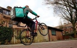 Utrecht, Nederland, 19 Februari, 2019: deliverooarbeider die wheely terwijl het hebben van voedsel in de zak maakt royalty-vrije stock foto's