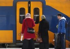 Utrecht, os Países Baixos, o 15 de fevereiro de 2019: Três pessoas que viajam com o trem e que esperam as portas para abrir imagens de stock royalty free