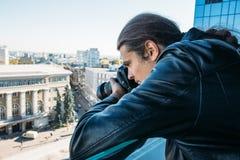 Utredare eller privat kriminalare eller reporter eller paparazzi som tar fotoet från balkong av byggnad med den yrkesmässiga kame fotografering för bildbyråer