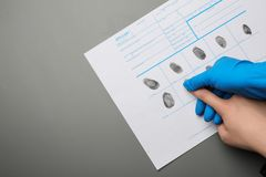 Utredare som tar fingeravtryck av misstänkten på grå bakgrund, bästa sikt med utrymme för text royaltyfri foto