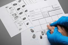 Utredare som tar fingeravtryck av misstänkten på tabellen, bästa sikt royaltyfria bilder