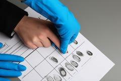 Utredare som tar fingeravtryck av misstänkten på tabellen, closeup arkivbild