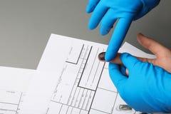 Utredare som tar fingeravtryck av misstänkten på tabellen, closeup royaltyfri bild