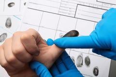 Utredare som tar fingeravtryck av misstänkten på tabellen, closeup royaltyfri foto
