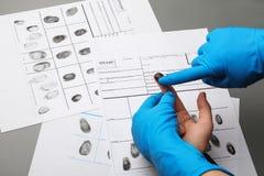 Utredare som tar fingeravtryck av misstänkten på tabellen, closeup royaltyfria foton